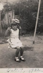 Shirley M. Perkins, age 6, on a swing set